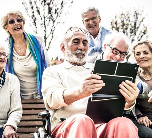 Elderly people around a bench watching a tablet