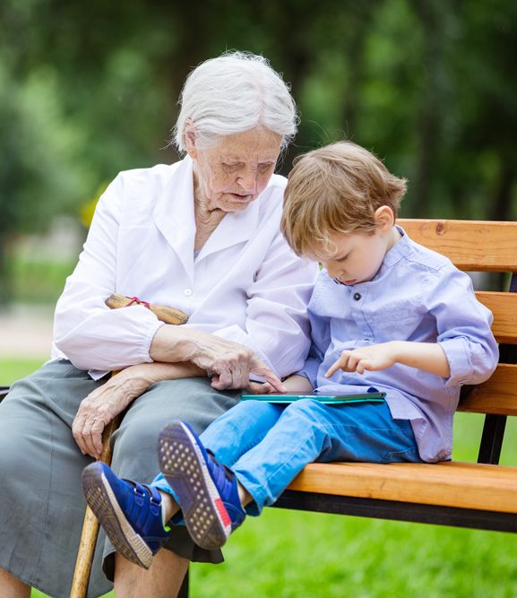 Elderly women works with child on tablet